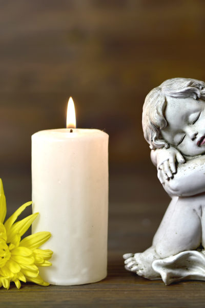 Angel, candle and flower on wooden background